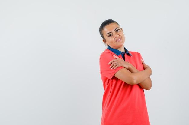 赤いシャツを着て腕を組んで立っているときれいに見える若い女性。正面図。