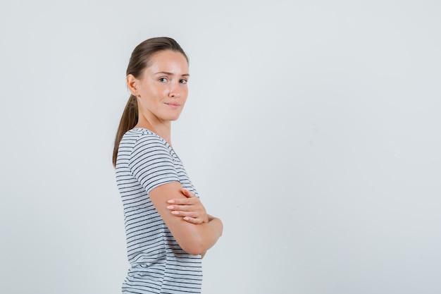 Молодая женщина стоя со скрещенными руками в футболке и выглядела весело.