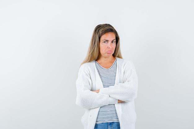 T- 셔츠, 재킷에 교차 팔으로 서 불쾌, 전면보기를 찾고 젊은 여자.