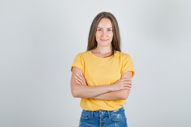 Молодая женщина стоит со скрещенными руками в футболке, шортах и выглядит весело