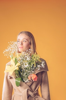 Young woman standing with flowers bouquet in coat