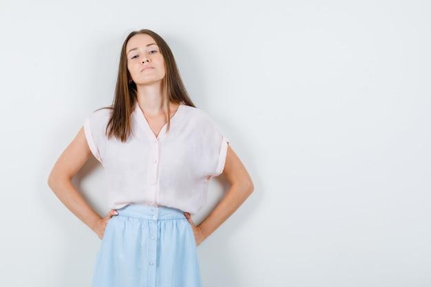 Молодая женщина, стоящая с руками на талии в футболке, юбке и уверенно выглядящая. передний план.