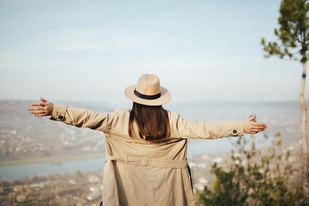 山の頂上に手を上げて立って、上から街を見ている若い女性。
