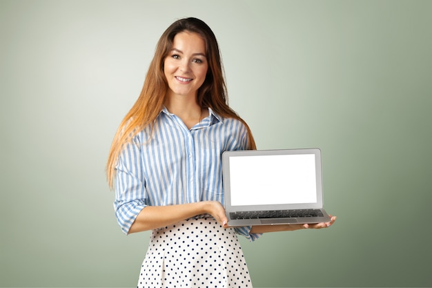 Young woman standing with laptop laptop in her hands
