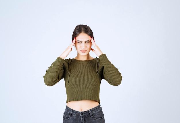 白い背景に痛みを伴う頭痛に立っている若い女性。