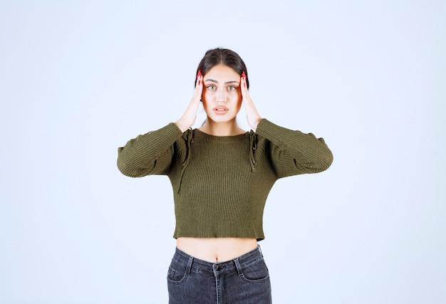 Giovane donna in piedi con doloroso mal di testa su sfondo bianco.