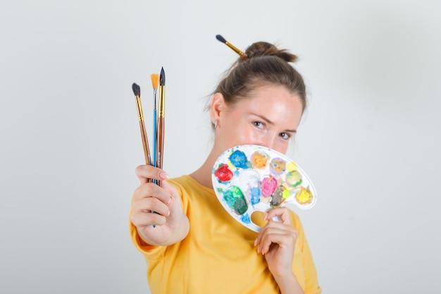Молодая женщина, стоящая с инструментами для рисования в желтой футболке и выглядящая счастливой