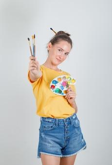 Молодая женщина стоит с инструментами для рисования в желтой футболке, джинсовых шортах и выглядит веселой