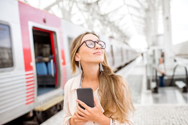 Молодая женщина, стоящая со смартфоном возле поезда на вокзале