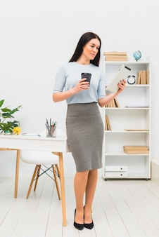 Young woman standing with tablet and coffee cup in office