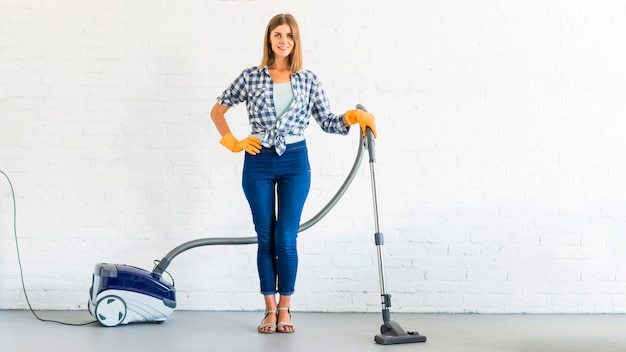 Young woman standing with vacuum cleaner in front of brick wall