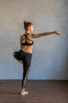 Young woman standing in a yoga exercise position. girl balancing, practice stretch exercise at yoga class - she is standing on one leg