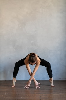 Young woman standing in a yoga exercise position. girl balancing, practice stretch exercise at yoga class.