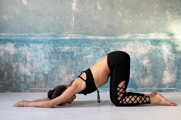 Young woman standing in a yoga position. girl practice stretch exercise at yoga class, doing push ups at home.