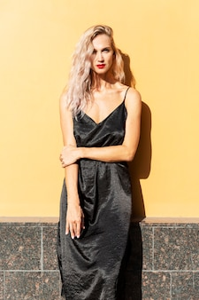 Young woman stands against a yellow wall of a building. beautiful blonde in a black dress in bright sunlight.