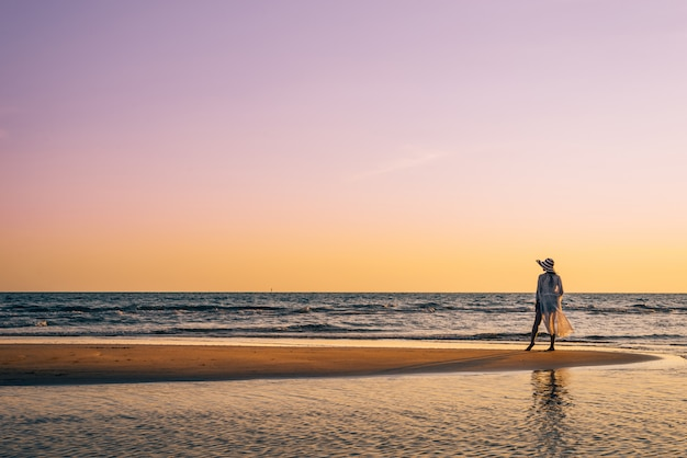 A young woman stands on the beach during a sunset, summer vacation.