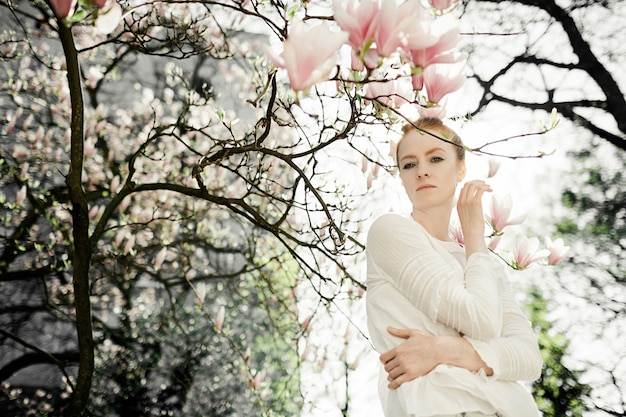 Young woman stands under blossom magnolia tree