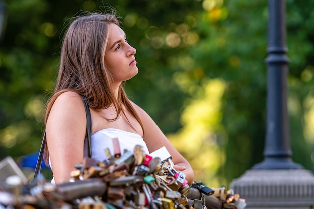 A young woman stands on a bridge with love locks and stares dreamily into the distance, defocused natural background