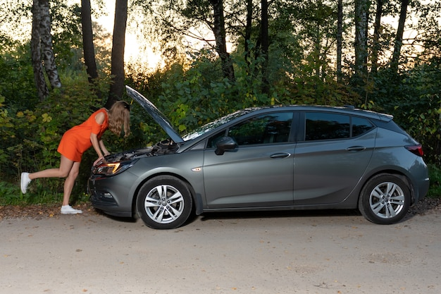 A young woman stands at a broken car and looks at the engine, does not understand how to repair