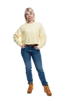 A young woman stands in full growth. smiling blonde in a yellow sweater and jeans.