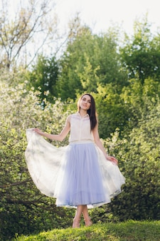 Young woman stands on a hill against the background of flowering trees