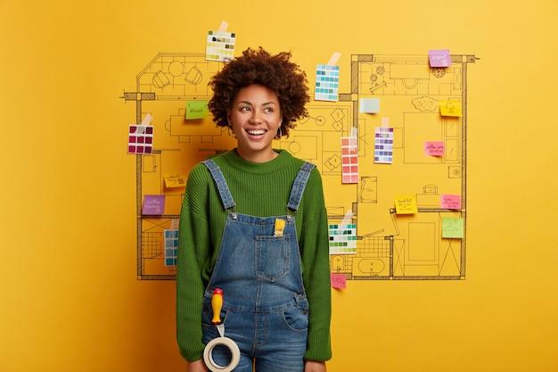 Giovane donna si trova accanto alla casa schizzo di design pronto per la ristrutturazione