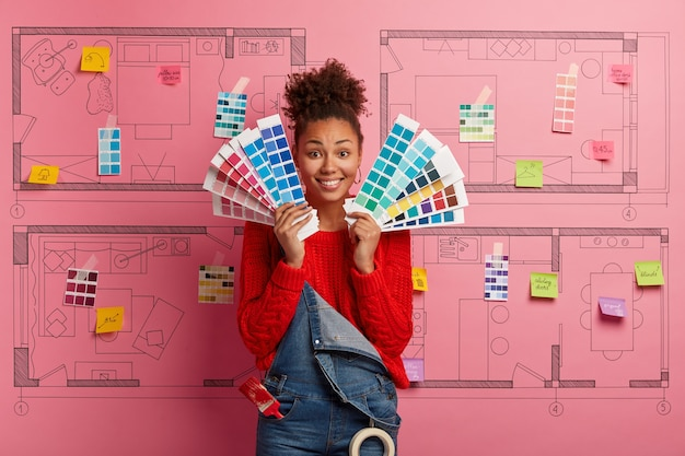 Young woman stands next to house design sketch ready for renovation