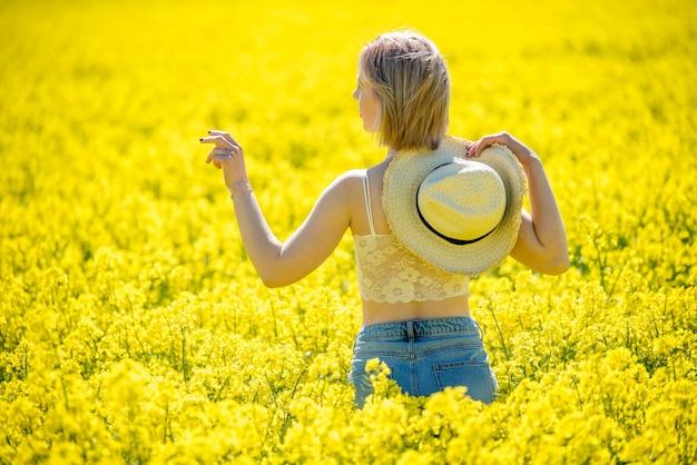 Молодая женщина стоит в поле изнасилования