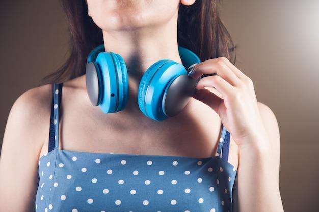 갈색 배경에 큰 헤드폰을 끼고 서 있는 젊은 여성