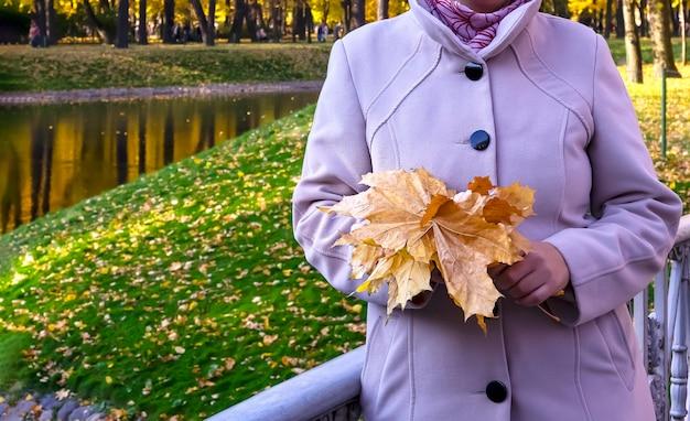 若い女性は橋の上の公園に立って、秋のカエデの葉の花束を持っています。体の一部。秋のロマンチックなコンセプト。