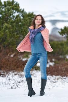 젊은 여자는 카메라를 보고 상록 침 엽 수 나무 근처 겨울 숲에 서 있다. 스카프, 청바지, 하이넥 데미 시즌 부츠가 달린 베이지색 재킷을 입은 긴 머리를 가진 귀여운 브루네트 여성