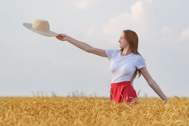 Young woman stands in middle of field of ripe wheat and holds straw hat