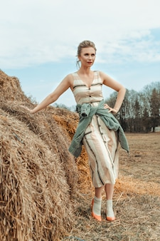 A young woman stands near a haystack with hay