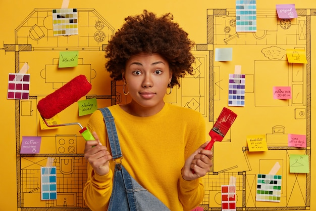 若い女性は、リフォームの準備ができて家の設計スケッチの隣に立っています