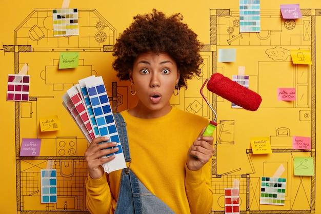 젊은 여자는 리노베이션을위한 준비가 집 디자인 스케치 옆에 서