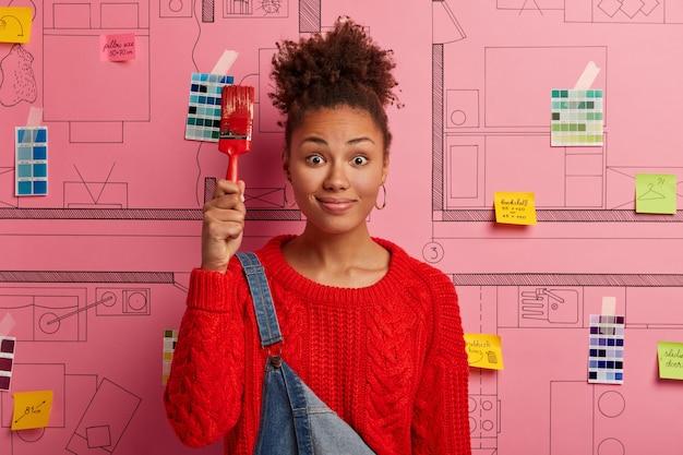 Молодая женщина стоит рядом с эскизом дизайна дома, готовым к ремонту