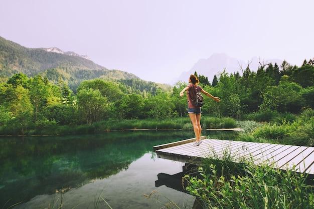 젊은 여성은 자연 배경 위에 팔을 들고 나무 다리 위에 서 있다