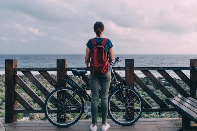 若い女性が海岸に立って海を見つめる