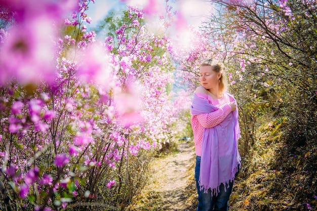 若い女性が立ち、休憩し、日光の下でシャクナゲの花の中で春に咲く庭を楽しんでいます。田舎での生活。