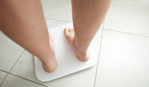 The young woman stands on the weight scales in the bathroom