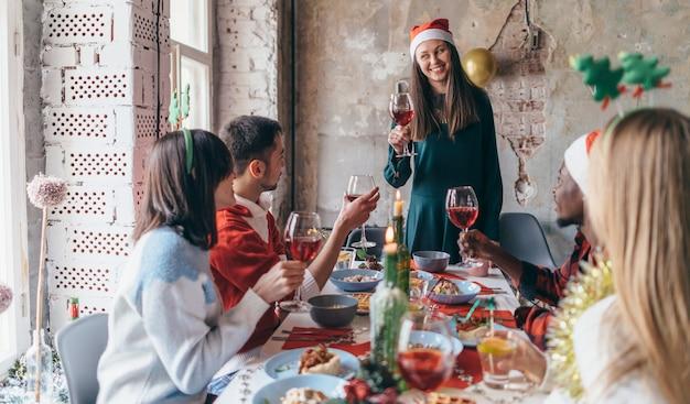 젊은 여성이 유리 잔을 들고 축배를하며 친구들이 축제 테이블에 앉아 있습니다.
