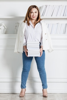 A young woman stands with books by a bookcase. smiling brunette in a white shirt, jacket and blue jeans. education and knowledge. full height. vertical. stylish interior.
