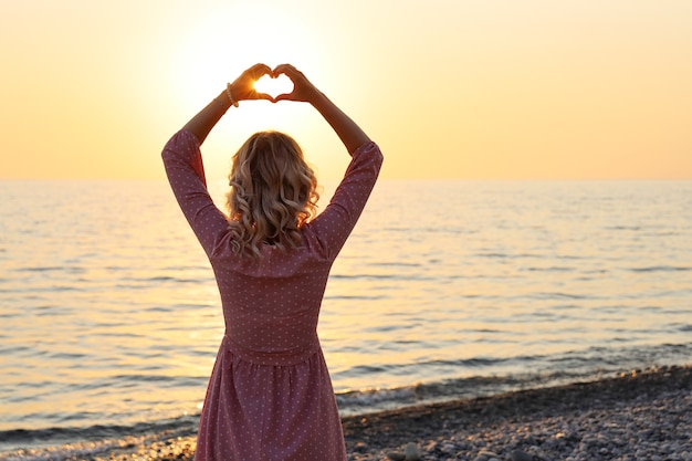 Young woman stands with her back on the shore with heart-shaped fingers above her head
