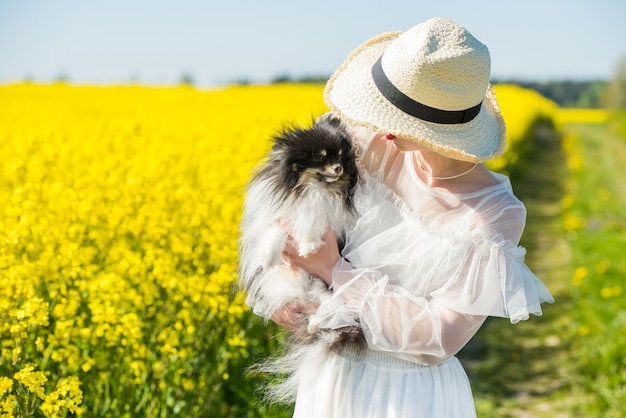 Young woman stands in a yellow field with dog