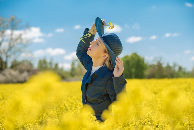 Young woman stands in a yellow field