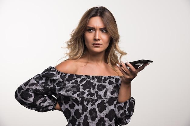 Молодая женщина, глядя в сторону, держа телефон на белой стене.