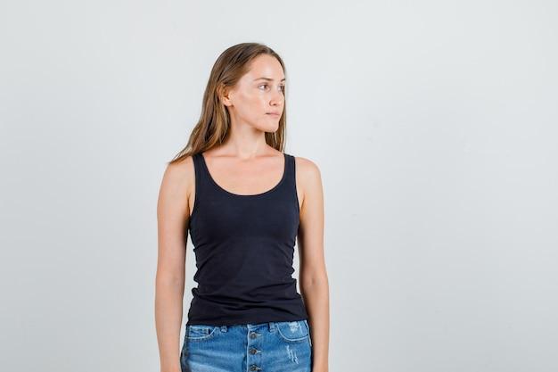 一重項、ショートパンツで横を見つめ、物思いにふける若い女性。正面図。