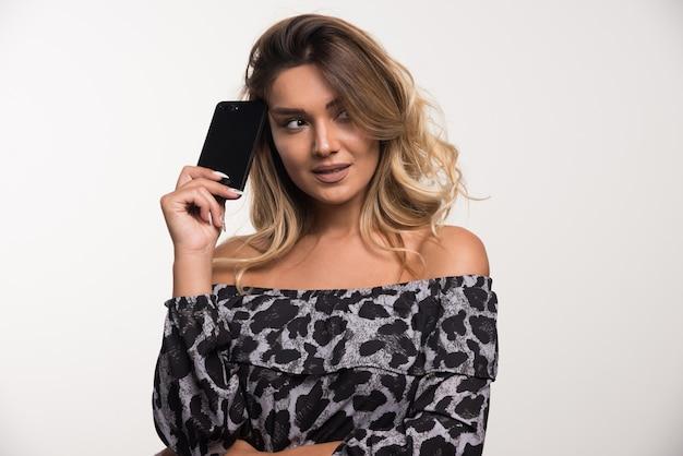 Молодая женщина смотрела, держа телефон на белой стене.