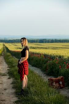 젊은 여자는 여름 시간에 시골 길에 가방 근처에 머물