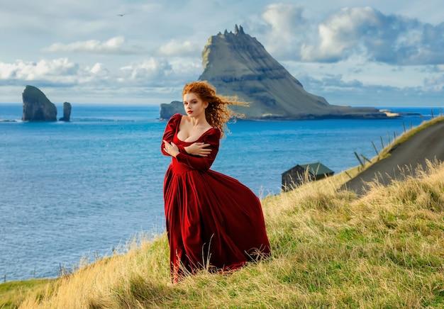若い女性は昔ながらの服で崖にとどまります。フェロー諸島